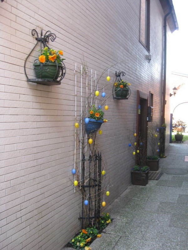Easter Garden Decoration. Fasten the flower pot on iron railing and cover some branches, hang yellow and blue Easter eggs on all the branches. You will get this beautiful garden design Easter decoration.