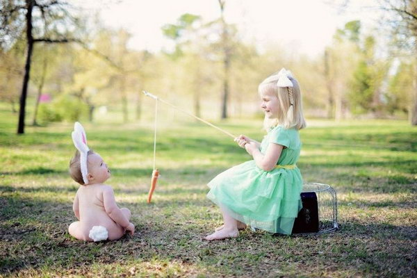 Adorable Sibling Easter Photo. The little girl is fishing, but she doesn't go for a fish, there is a carrot hang with the fishing rod. The little baby, the girl's little brother with the bunny ears looks like the rabbit. This sibling Easter photo is just so interesting.