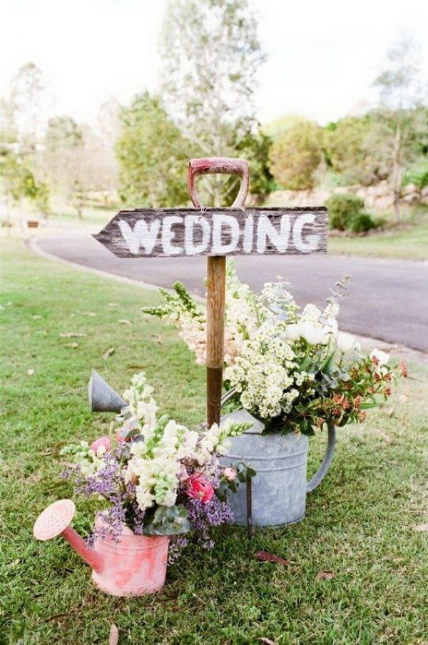 Rustic Wedding Wooden Sign. Finish off your rustic wedding theme with this wooden wedding sign to point the right direction for your guests. Prop it up with pitch for or garden shovel. It's fantastic to use watering cans as flower holders to add up some decorations.
