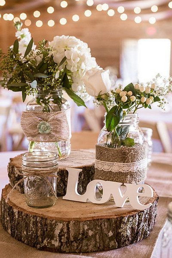 Burlap-Wrapped Mason Jars Stacked atop Tree Trunk Slices